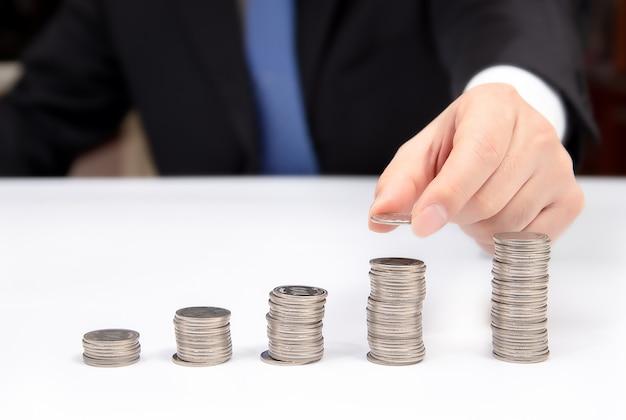 Ręka biznesowego mężczyzna wypiętrza monety. finansowe.