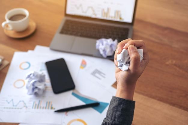 Ręka bizneswoman schrzanił dokumenty z laptopem i telefonem komórkowym na stole w biurze