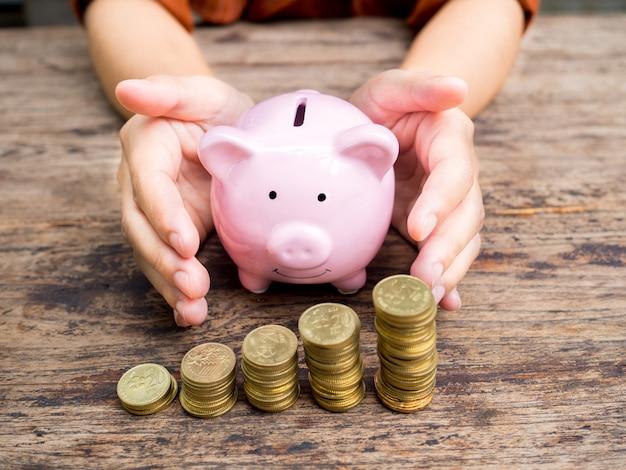 Ręka bizneswoman zapobiega różowa skarbonka ze stosem złotych monet oszczędzanie pieniędzy na fundusz emerytalny