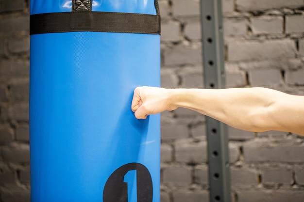 Ręka boksera i niebieską torbę treningową na siłowni.