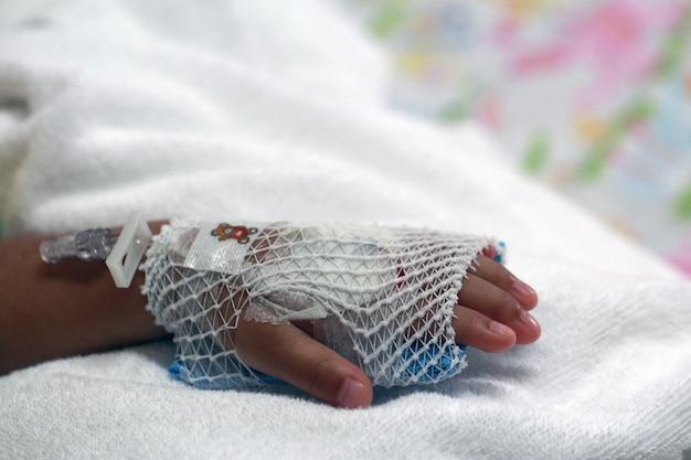 Ręka chorego dziecka przygotowuje się do dożylnego roztworu soli fizjologicznej w gospodarzu.