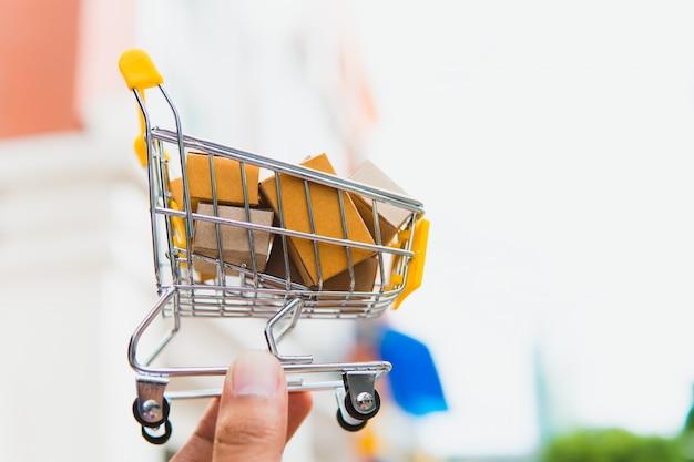 Ręka chwyta papierowy pudełko w mini wózek na zakupy używać jako handel elektroniczny, zakupy online i biznesowy marketingowy pojęcie