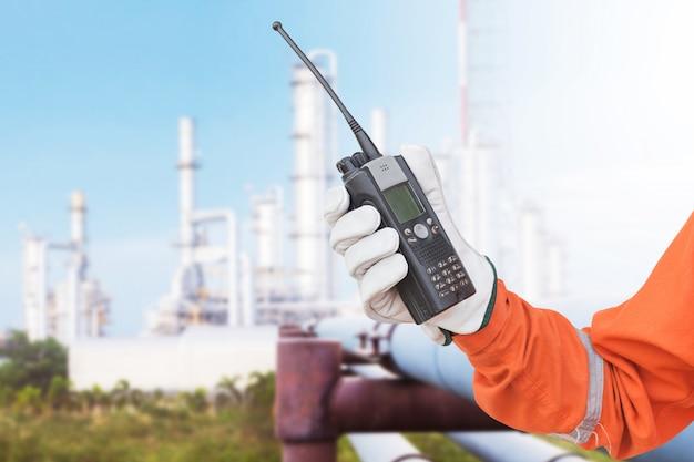 Ręka chwyta walkie talkie rafinerii ropy naftowej destylacja góruje tło