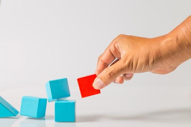Ręka ciągnie czerwony drewniany blok z błękitnych drewnianych bloków