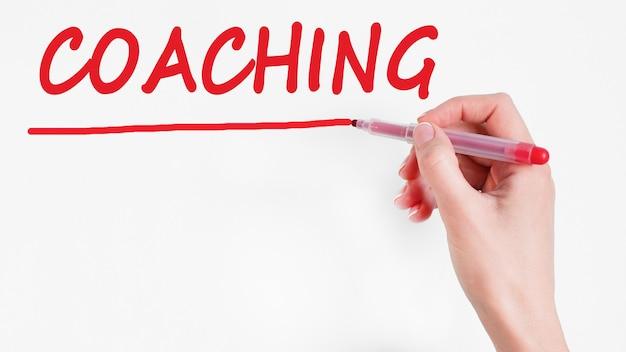 Ręka coaching napis napis z markerem w kolorze czerwonym