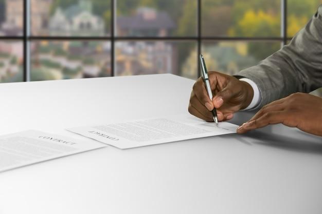 Ręka czarnego biznesmena podpisuje umowę. mężczyzna podpisywania umowy w ciągu dnia. możliwość zdobycia świetnej pracy. bezpieczeństwo jest gwarantowane.