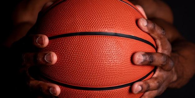 Ręka czarny człowiek trzyma piłkę do koszykówki