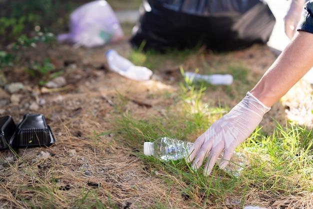 Ręką człowieka dotknąć plastikowej butelki w odkrytym parku