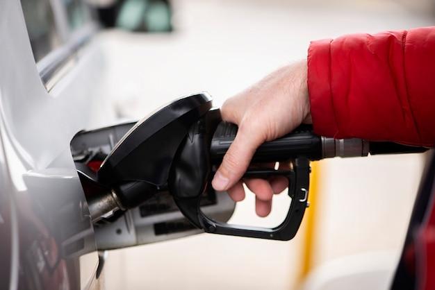 Ręką człowieka jest tankowanie benzyny lub oleju na stacji paliw przygotowującej transport do podróży