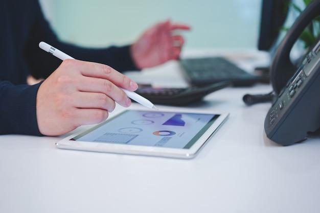 Ręka człowieka na tablecie z pulpitu nawigacyjnego wykres giełdowy