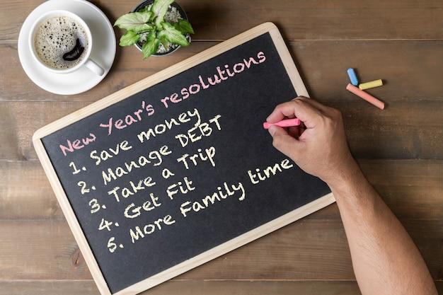 Ręką człowieka pisania rezolucji nowego roku na czarnej tablicy