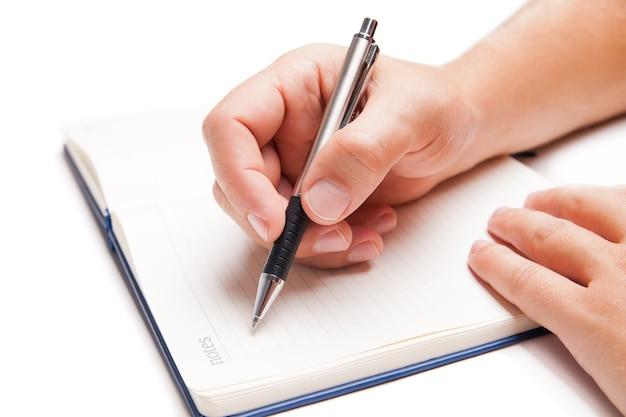 Ręka człowieka pisania w otwartej księdze na białym tle