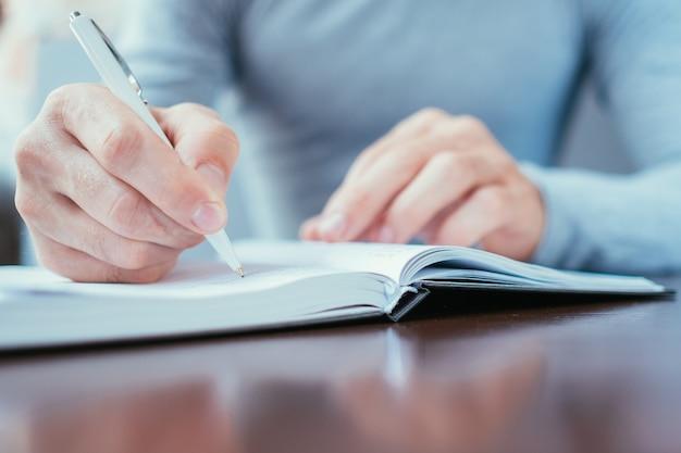 Ręka człowieka, pisząc w terminarz. harmonogram pracy i koncepcja osobistego organizatora.