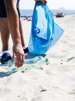 Ręką człowieka podnoszenia śmieci plastikową butelkę przy plaży trzymając niebieski worek na śmieci