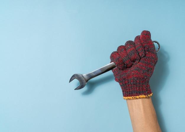 Ręka człowieka trzymać narzędzie klucza na niebieskim tle. skopiuj miejsce.