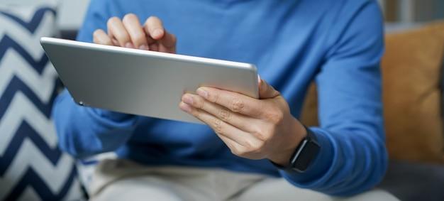 Ręka człowieka trzymającego cyfrowy tablet do korzystania z aplikacji lub mediów społecznościowych lub wyszukiwania w witrynie
