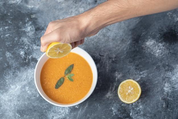 Ręka człowieka wyciskając plasterek cytryny do zupy z soczewicy.