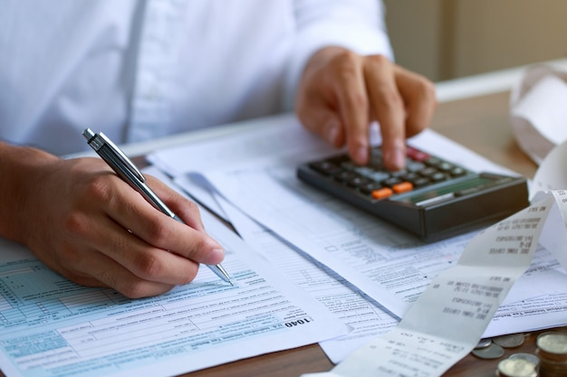 Ręką człowieka wypełniając formularz podatkowy usa formularz podatkowy nas biuro dochodów biznesowych dokument finansowy koncepcja podatku