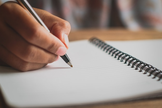 Ręką człowieka z piórem pisania na notebooku. trzymaj ręce długopisem. biel na biurku, wzory drewna z natury, pisanie książki.