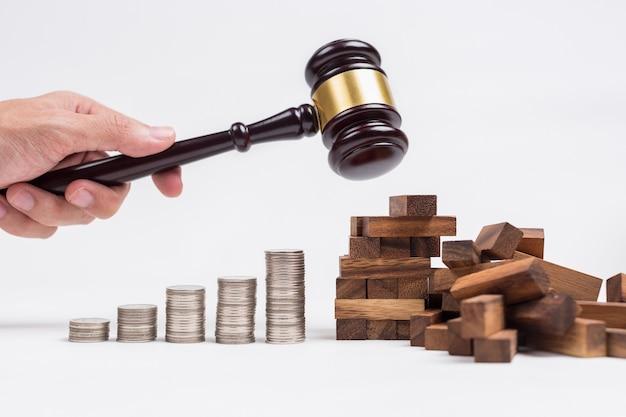 Ręka człowieka za pomocą drewna młotek zniszczyć zabawki drewniane budynku obok rzędu monet.