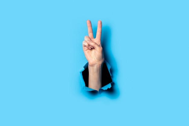 Ręka czyni gest dwoma palcami w górę na niebiesko
