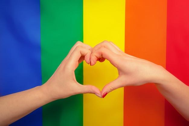 Ręka czyni znak serca z tęczową flagą gejowskiej dumy lgbt