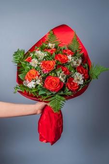 Ręka dając kwiaty. układ bukietów. koncepcja walentynkowa lub życzenia świąteczne