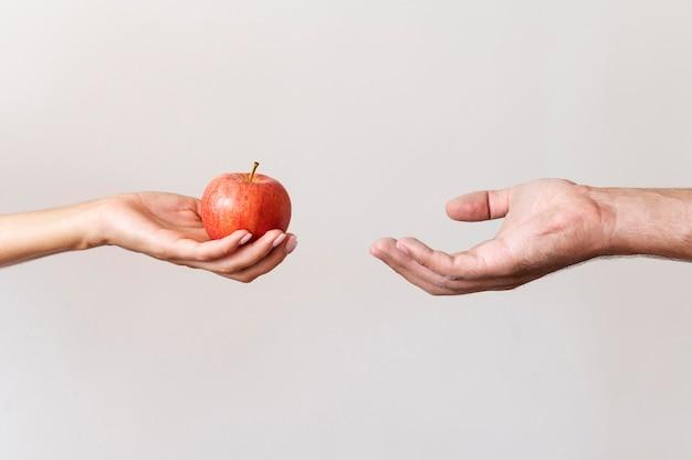 Ręka dająca jabłko potrzebującej osobie