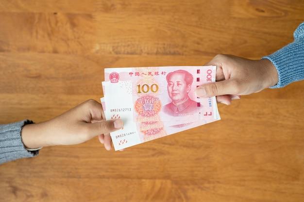 Ręka daje banknoty chińskiego juana