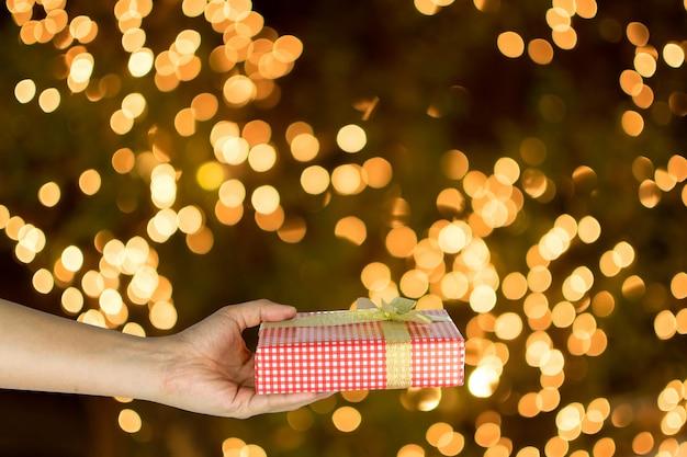 Ręka daje czerwonym prezenta pudełku na bielu