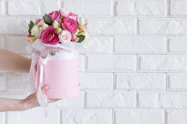 Ręka daje kilka różowych i żółtych róż na tle białej cegły. prezent dla mamy lub kobiety, praca kwiaciarni, dekoracje ślubne, koncepcja sprzedaży pięknych bukietów