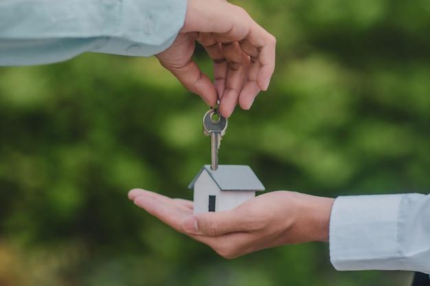 Ręka daje kluczowe ubezpieczenie wynajmu sprzedaży domu biznesowego