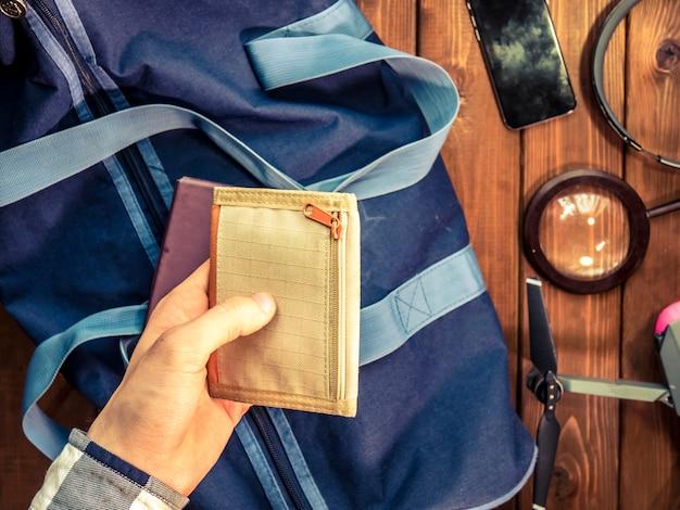 Ręka daje koncepcji podróży portfel nad drewnianym stołem
