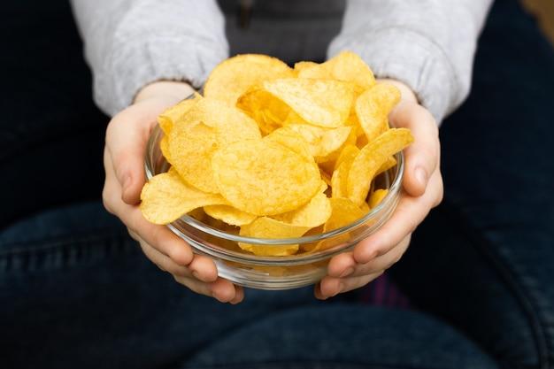 Ręka daje misce chrupiące chipsy ziemniaczane.