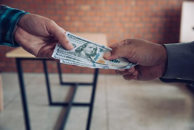 Ręka daje pieniądze - dolary amerykańskie. ręka odbiera pieniądze od biznesmena. pojęcie korupcji