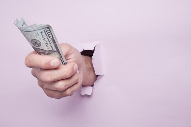 Ręka daje pieniądze przez dziury na papierze