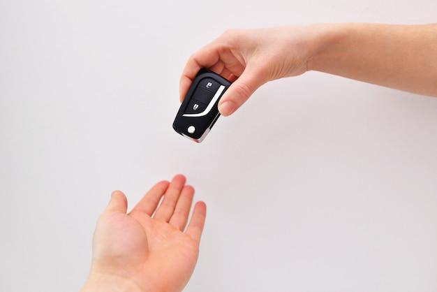 Ręka daje zbliżenie kluczyk samochodowy na białym tle na tle, zbliżenie. uzyskanie prawa jazdy.