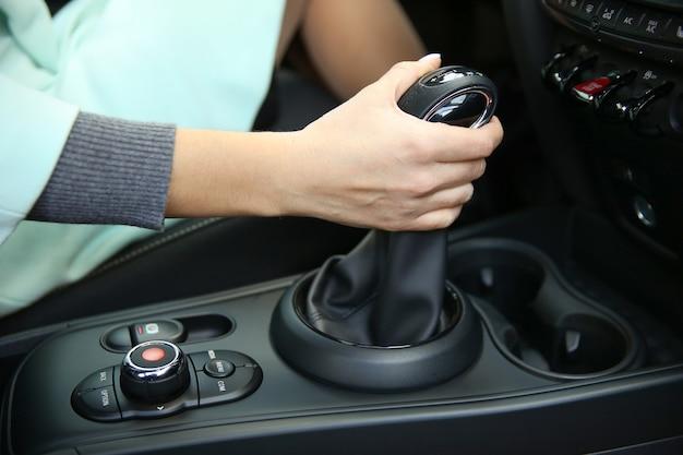 Ręka damska jest na dźwigni zmiany biegów zbliżenie automatycznej skrzyni biegów