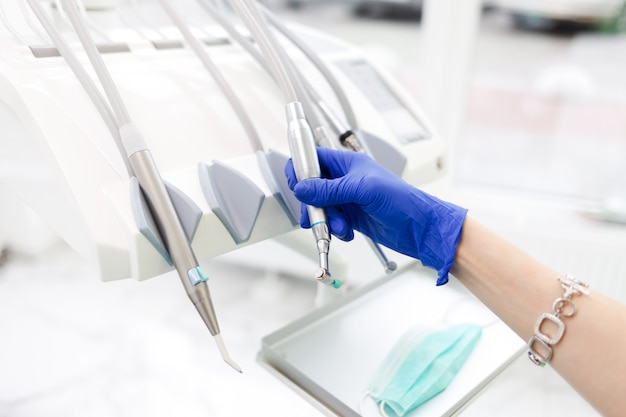 Ręka dentysty bierze jedną z wielu wierteł. koncepcja sprzętu stomatologicznego