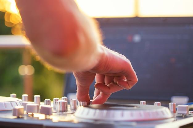 Ręka dj'a miksuje dźwięk na panelu sterowania