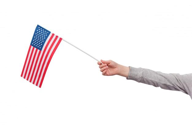Ręka dla dzieci trzyma flagę usa na białym tle na białej przestrzeni. flaga stanów zjednoczonych ameryki