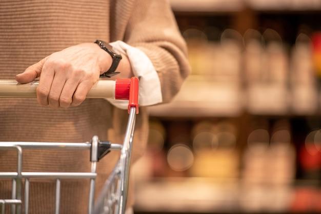 Ręka dojrzałej klientki współczesnego supermarketu pchająca koszyk z towarami podczas wizyty w jednym z działów