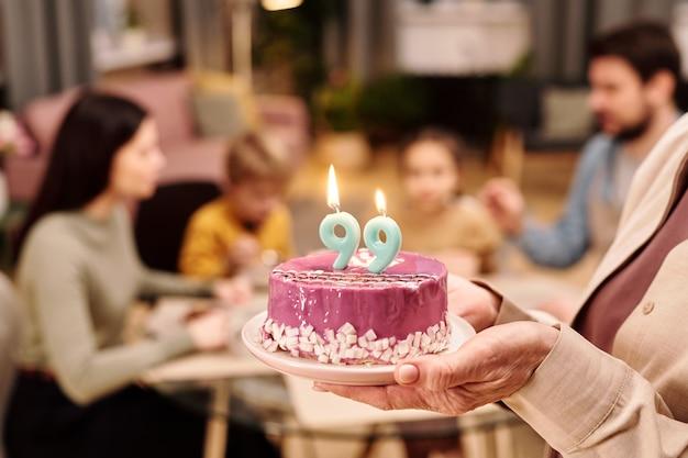 Ręka dojrzałej kobiety trzymającej tort urodzinowy z dwiema świeczkami w kształcie dziewięciu