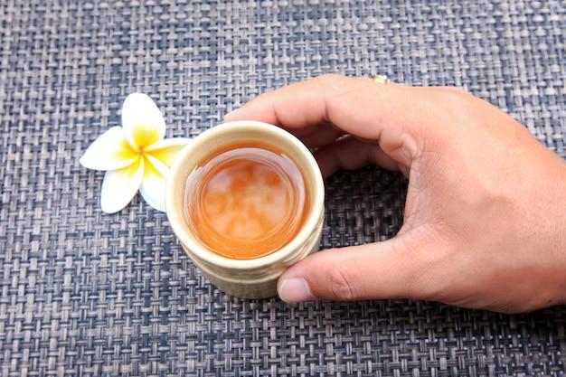 Ręka dotyka filiżankę gorącej herbaty z kwiatem frangipani na maty bambusowe