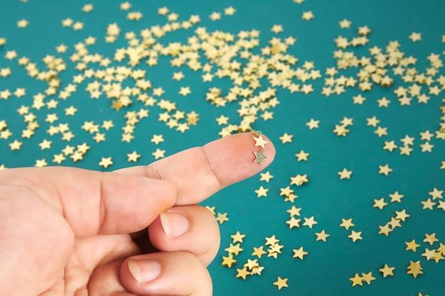 Ręka dotyka litych konfetti w formie gwiazdek. pojęcie dotyku, wrażliwości dotykowej, uczuć.