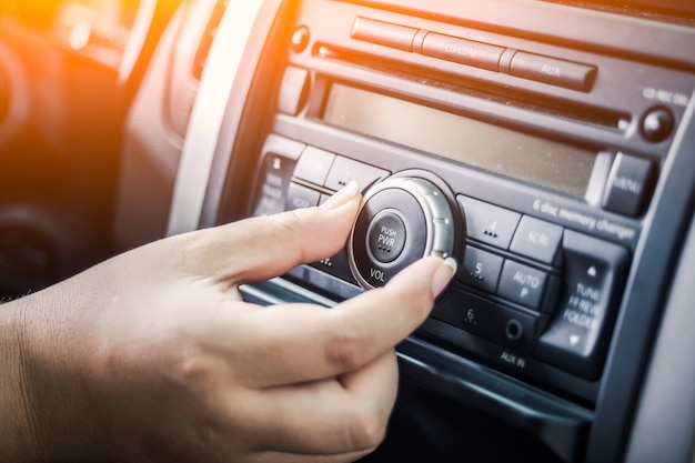 Ręka dotyka pokrętła radia