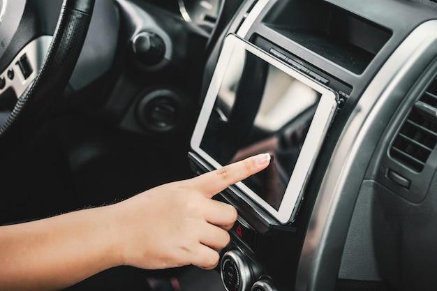 Ręka dotyka tabletu w samochodzie