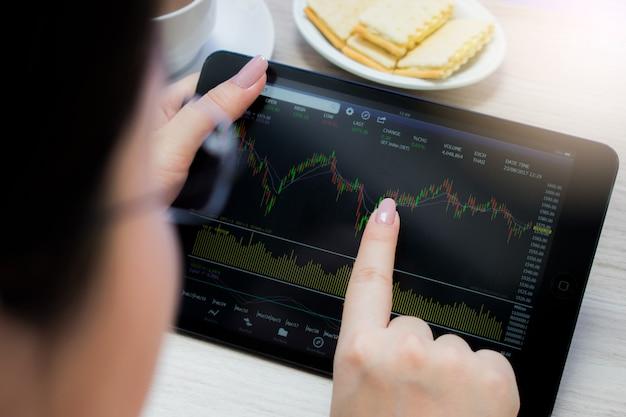 Ręka dotyka wykresu giełdowego na tablecie. handel na koncepcji rynku akcji.