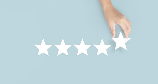 Ręka dotykająca wznosi się na pięć gwiazdek. zwiększenie oceny oceny i koncepcji klasyfikacji