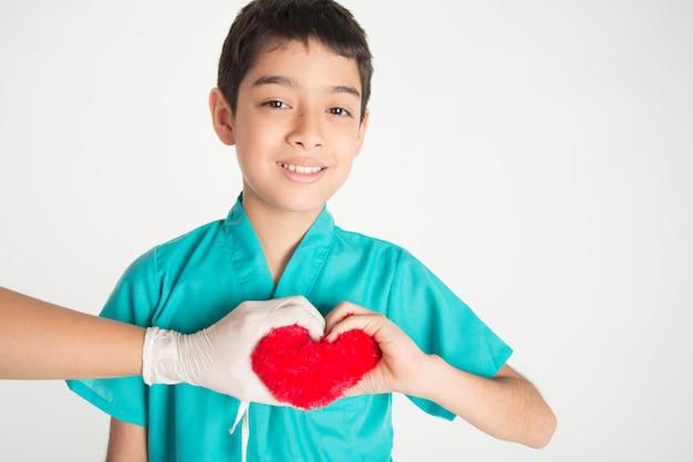 Ręka dziecka i lekarza dotykają się nawzajem sercem w dłoni